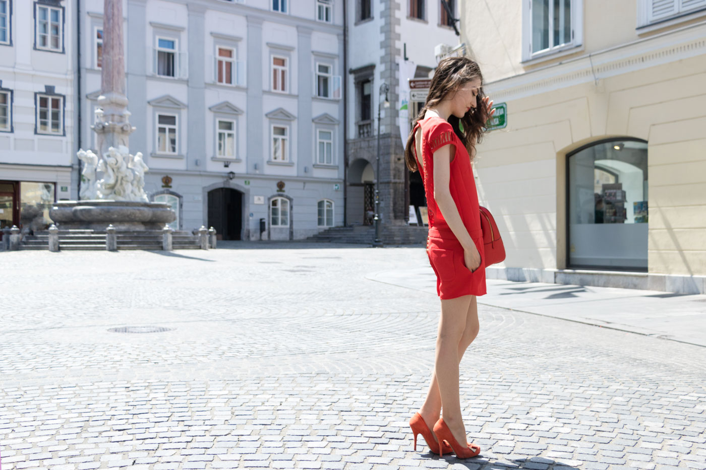Fashion Blogger Veronika Lipar of Brunette from Wall Street wearing red playsuit with the open back, red heels and red Michael Kors tote bag