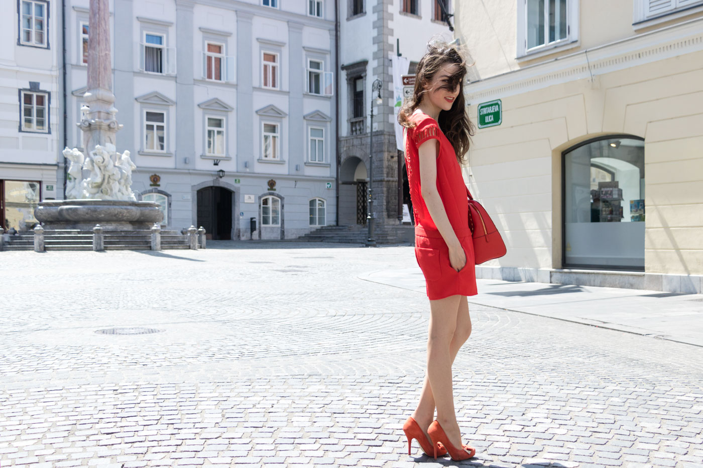 Fashion Blogger Veronika Lipar of Brunette from Wall Street wearing red romper with the open back, red pumps and red Michael Kors tote bag