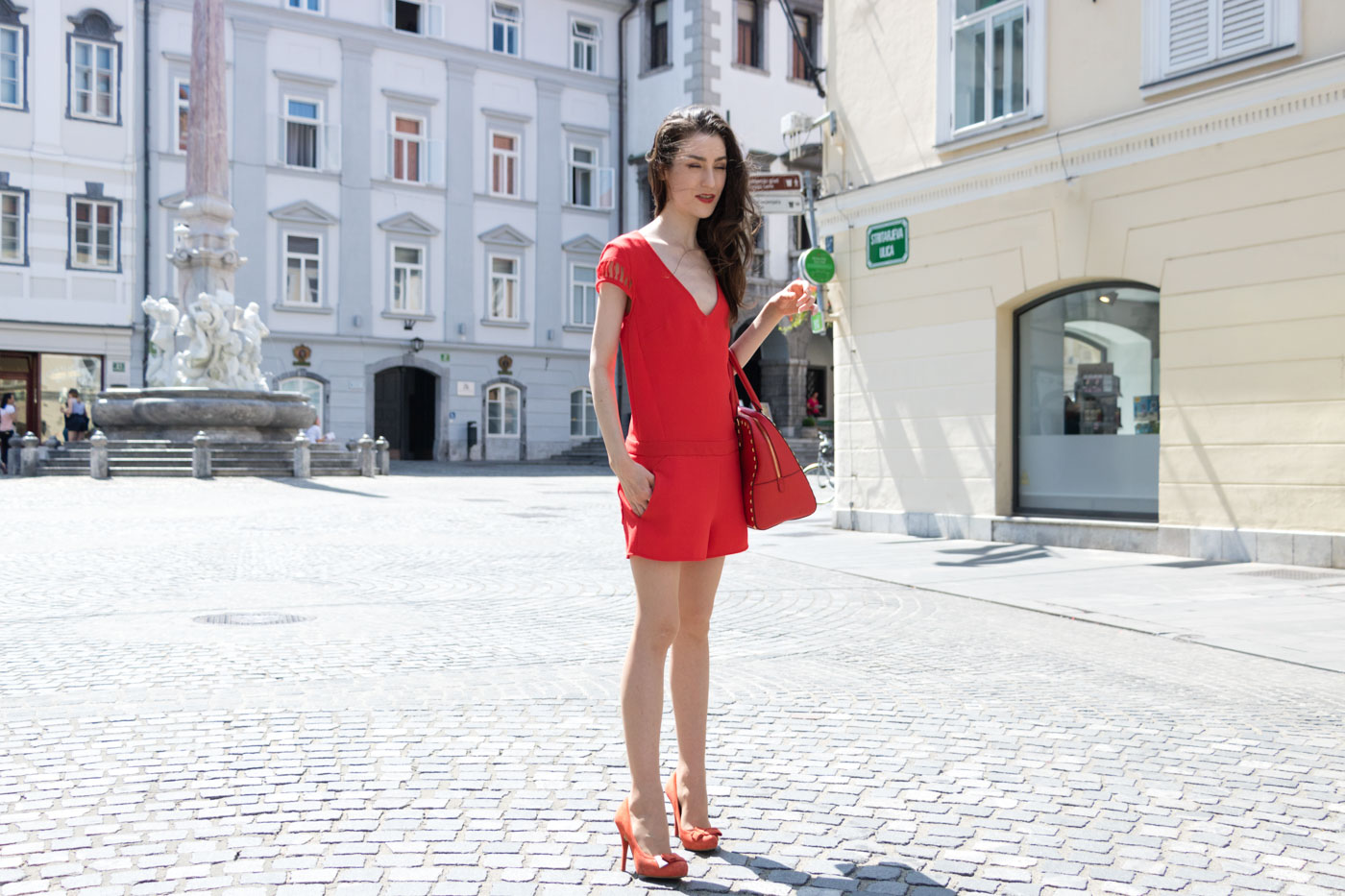 Fashion Blogger Veronika Lipar of Brunette from Wall Street wearing red playsuit with the open back, red pumps and red Michael Kors tote bag