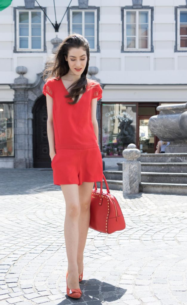 Fashion Blogger Veronika Lipar of Brunette from Wall Street wearing red playsuit with the open back, red heels and red Michael Kors tote bag on the streets of Ljubljana