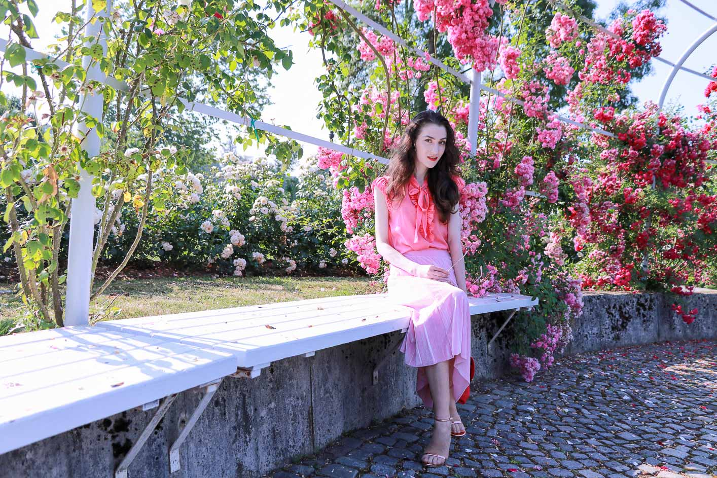 Fashion Blogger Veronika Lipar of Brunette from Wall Street wearing bold red lips, highlighter, pink round sunglasses, pink pleated skirt, pink top handle bag and pink ruffled blouse