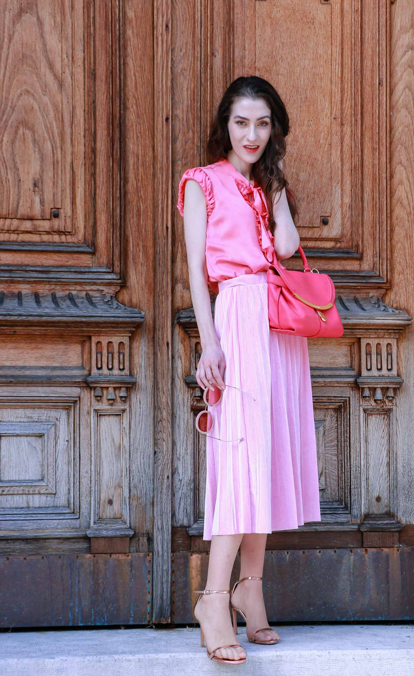 Fashion Blogger Veronika Lipar of Brunette from Wall Street wearing round pink sunglasses from Sunday Somewhere, pink pleated midi skirt, pink top, hot pink top handle bag and metallic rose gold sandals when leaving home
