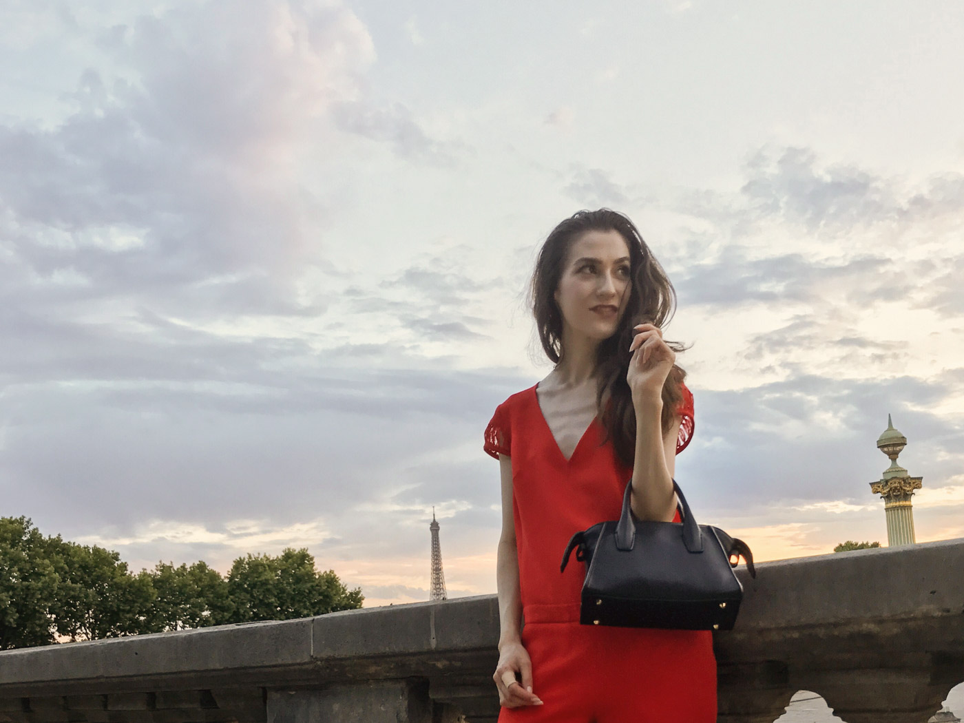 Fashion Blogger Veronika Lipar of Brunette from Wall Street standing by the Eiffel Tower in the red outfit