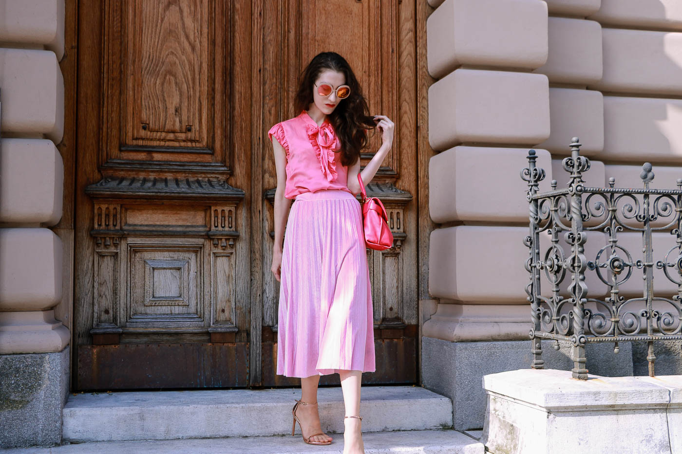 Fashion Blogger Veronika Lipar of Brunette from Wall Street wearing velvet pink midi skirt with pleats and metallic rose gold sandals while leaving home