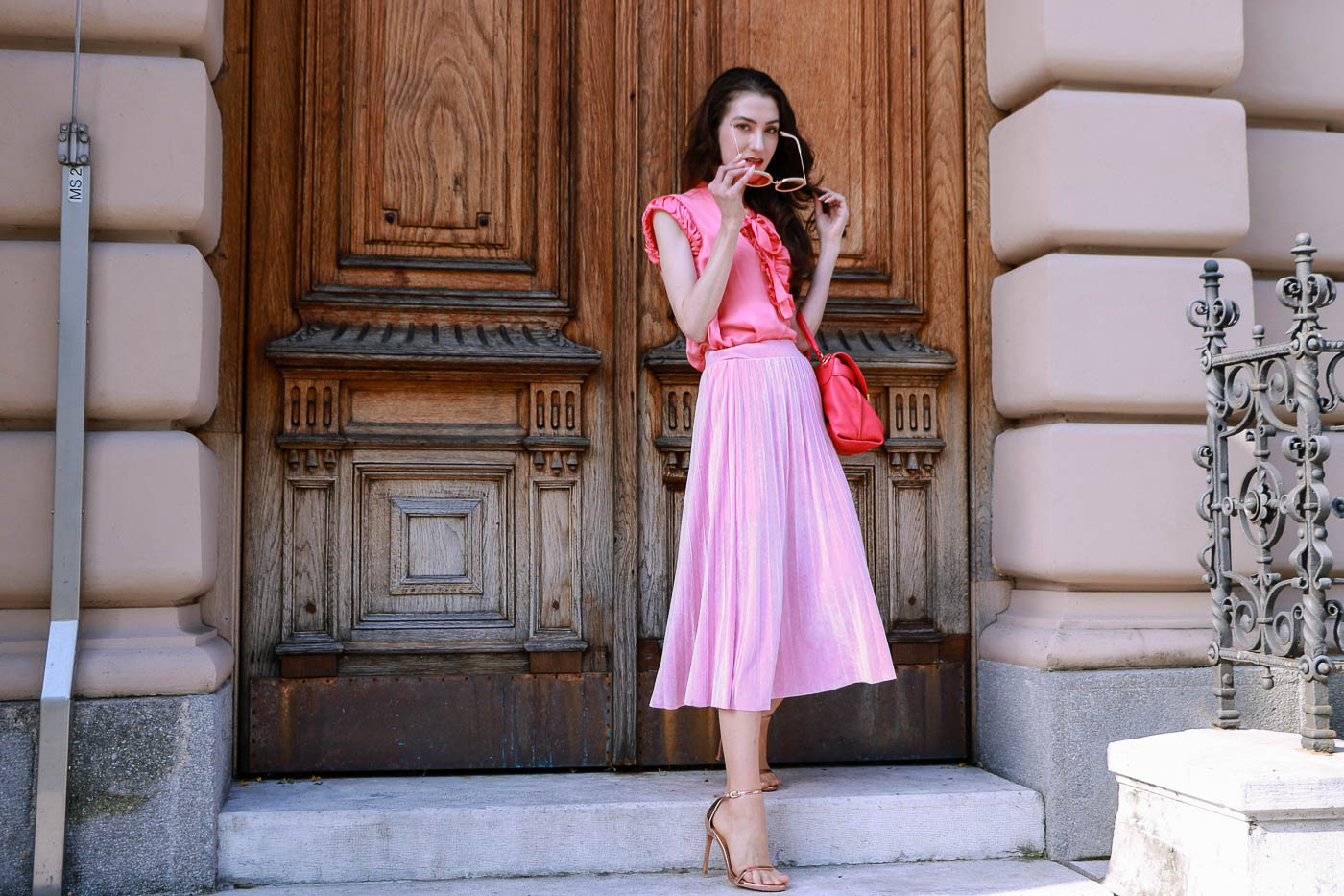Fashion Blogger Veronika Lipar of Brunette from Wall Street wearing round framed sunglasses, pink pleated midi skirt, pink top, hot pink top handle bag and metallic rose gold sandals while standing at the door