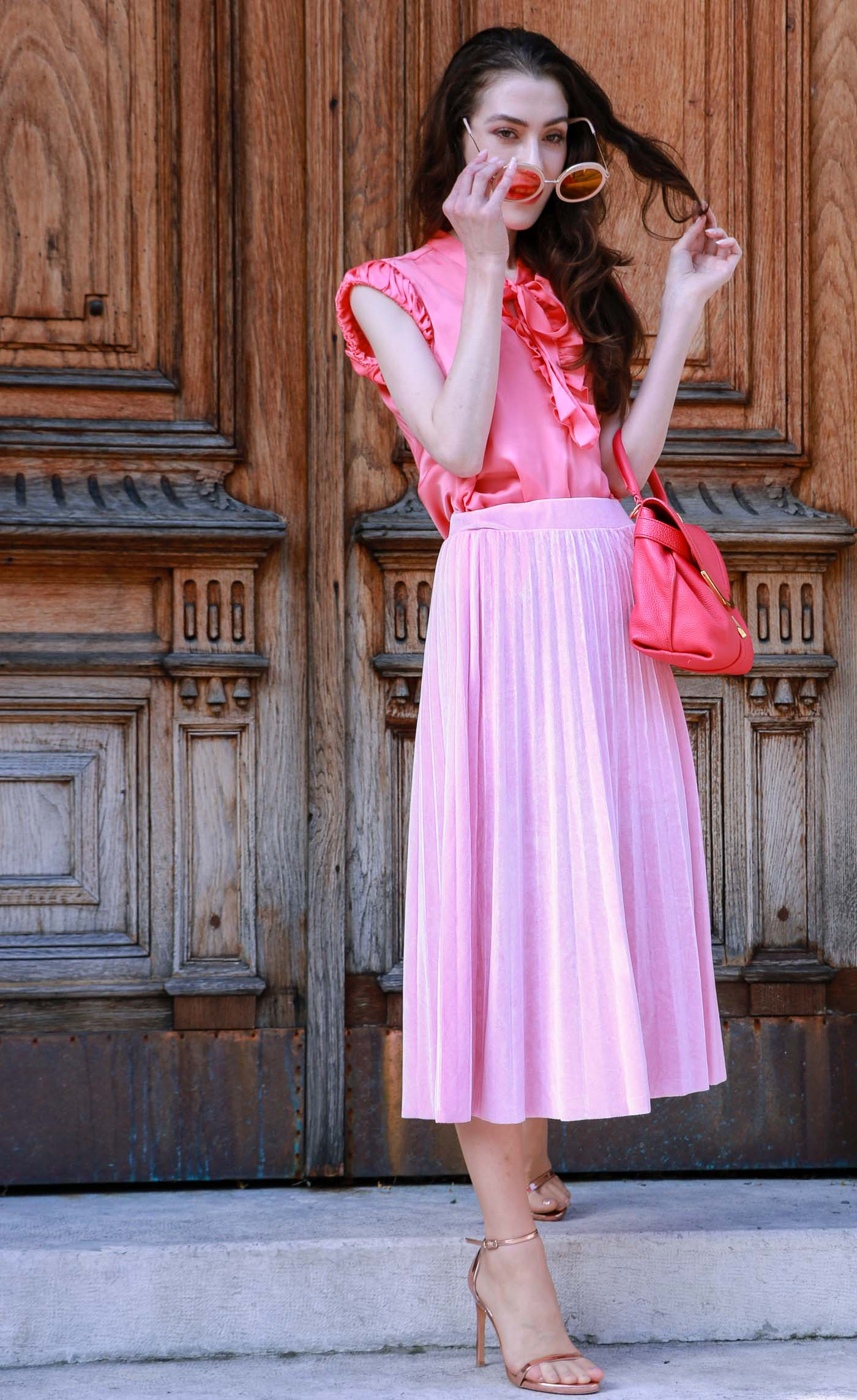 Fashion Blogger Veronika Lipar of Brunette from Wall Street wearing round pink sunglasses from Sunday Somewhere, pink pleated midi skirt, pink top, hot pink top handle bag and metallic rose gold sandals while standing at the door