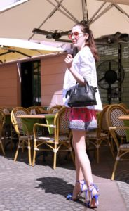 Fashion Blogger Veronika Lipar of Brunette from Wall Street dressed in round pink sunglasses from Sunday Somewhere, printed pink silk shorts, printed top, white blazer, blue aquazzura sctrappy sandals, small black bag and a sleek ponytail while walking down the street in Ljubljana