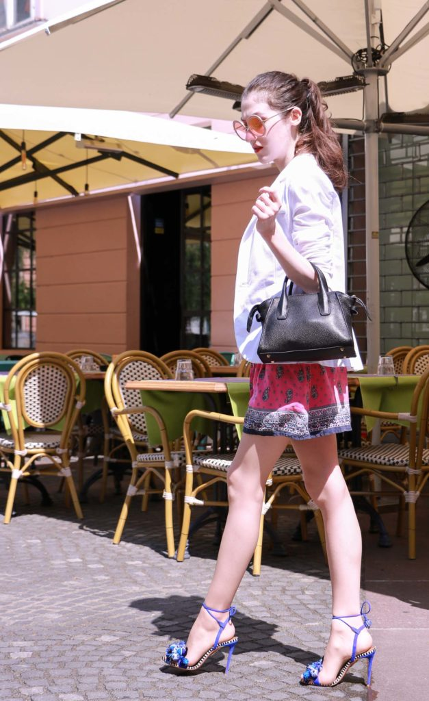 Fashion Blogger Veronika Lipar of Brunette from Wall Street dressed in round pink sunglasses from Sunday Somewhere, printed pink silk shorts, printed top, white blazer, blue aquazzura sctrappy sandals, small black bag and a sleek ponytail while posing on a street in Ljubljana