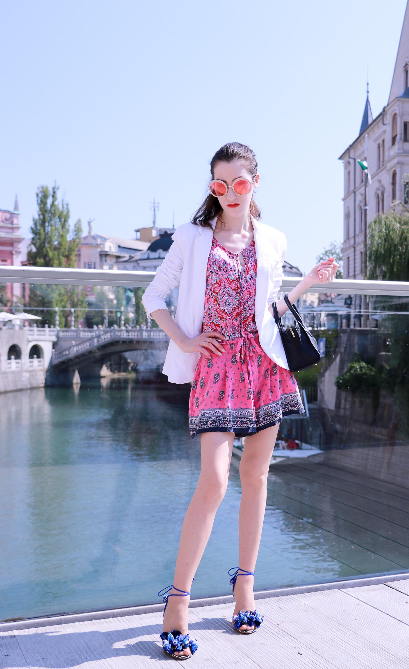 Fashion Blogger Veronika Lipar of Brunette from Wall Street wearing round pink sunglasses from Sunday Somewhere, printed pink silk shorts, printed top, white blazer, blue aquazzura sctrappy sandals, small black bag and a sleek ponytail while standing on the bridge and looking the city