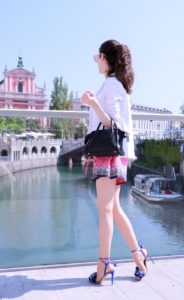 Fashion Blogger Veronika Lipar of Brunette from Wall Street dressed in round pink sunglasses from Sunday Somewhere, printed pink silk shorts, printed top, white blazer, blue aquazzura sctrappy sandals, small black bag and a sleek ponytail while standing on the bridge and looking the city
