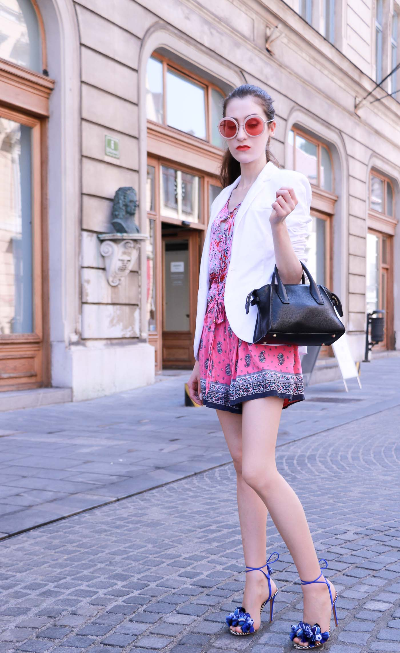 Fashion Blogger Veronika Lipar of Brunette from Wall Street wearing round pink sunglasses from Sunday Somewhere, printed pink silk shorts, printed top, white blazer, blue aquazzura sctrappy sandals, small black bag and a sleek ponytail while walking down the street in Ljubljana