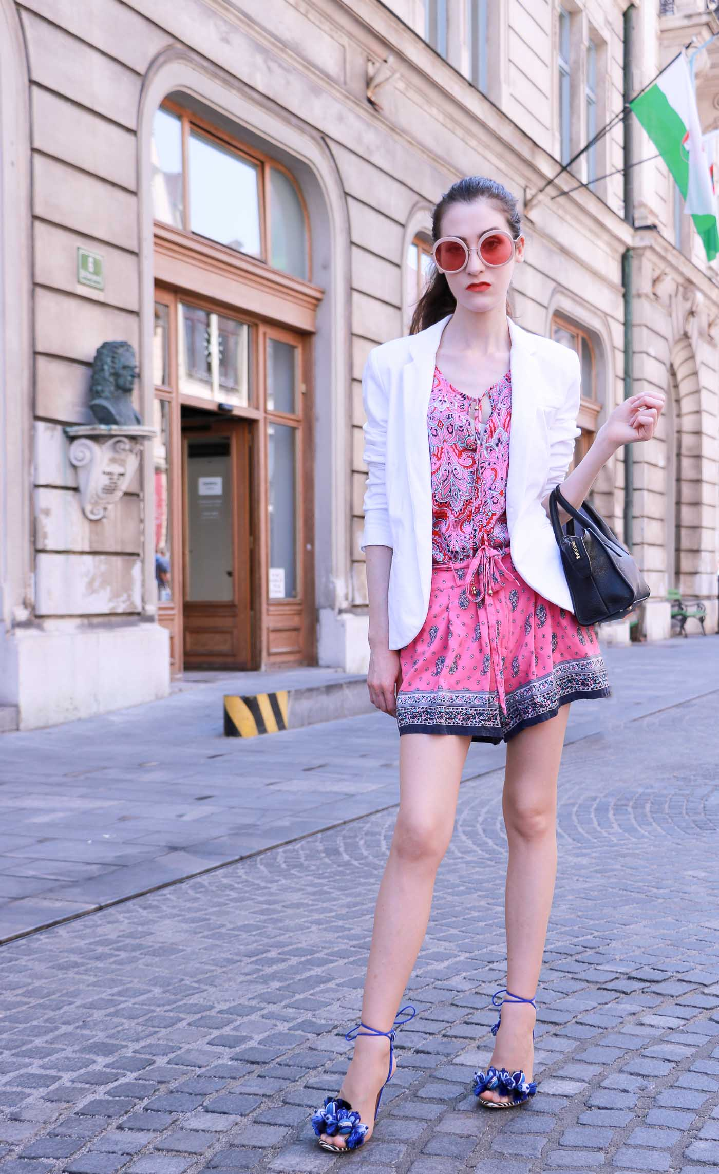 Fashion Blogger Veronika Lipar of Brunette from Wall Street wearing round pink sunglasses from Sunday Somewhere, printed pink silk shorts, printed top, white blazer, blue aquazzura sctrappy sandals, small black bag and a sleek ponytail while posing on a street in Ljubljana