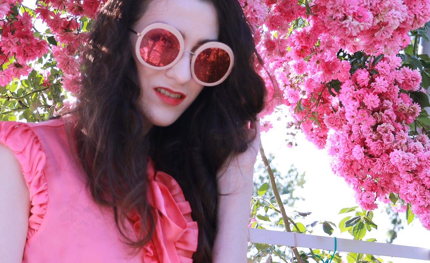 Fashion Blogger Veronika Lipar of Brunette from Wall Street wearing bold red lips, highlighter, pink round sunglasses