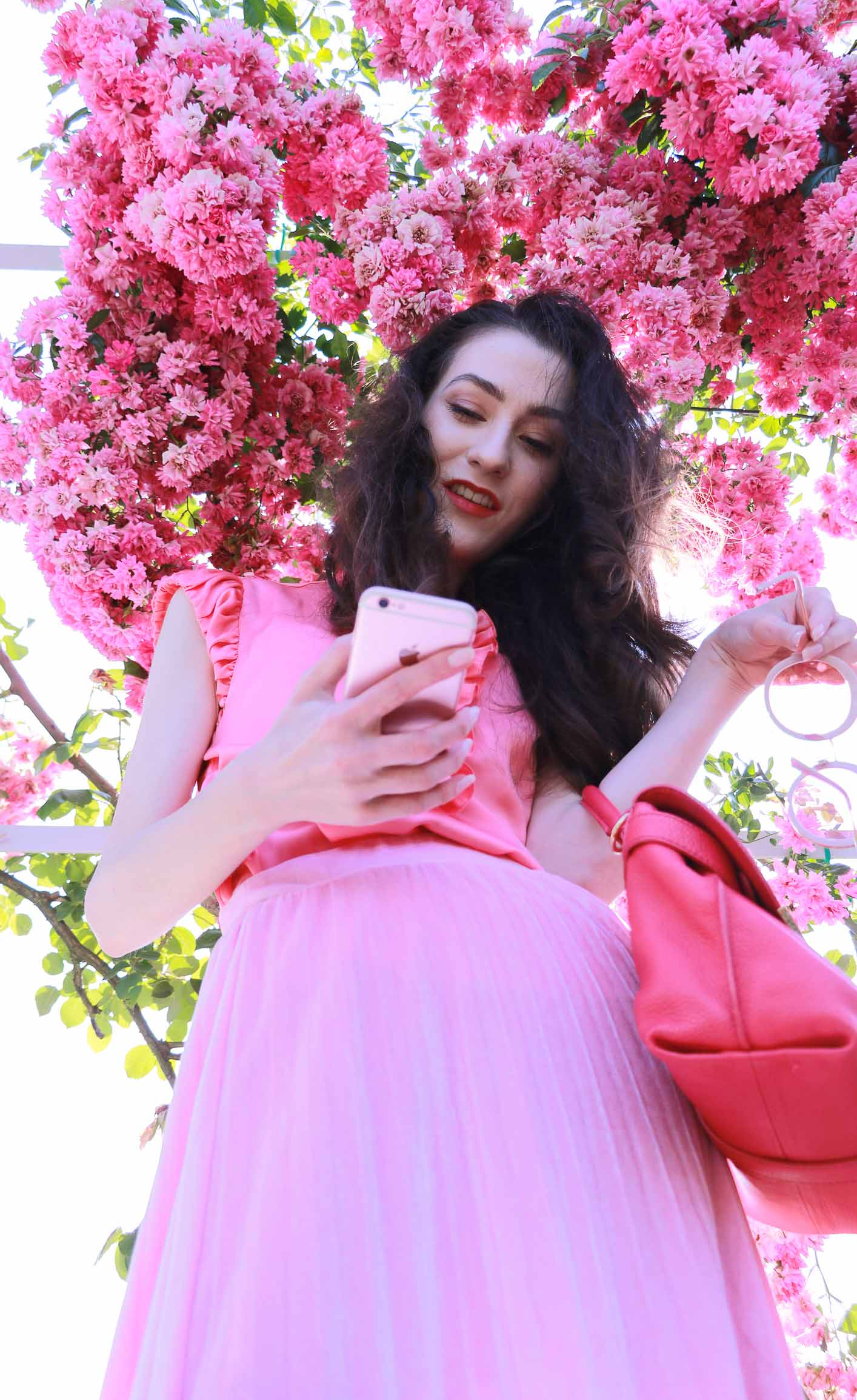 Fashion Blogger Veronika Lipar of Brunette from Wall Street wearing bold red lips, glowing makeup, pink round sunglasses, pink pleated skirt, pink top handle bag and pink ruffled blouse