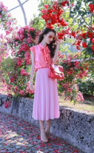 Fashion Blogger Veronika Lipar of Brunette from Wall Street wearing bold red lipstick, glowing makeup, pink round sunglasses, pink pleated midi skirt, pink top handle bag and pink ruffled bow blouse