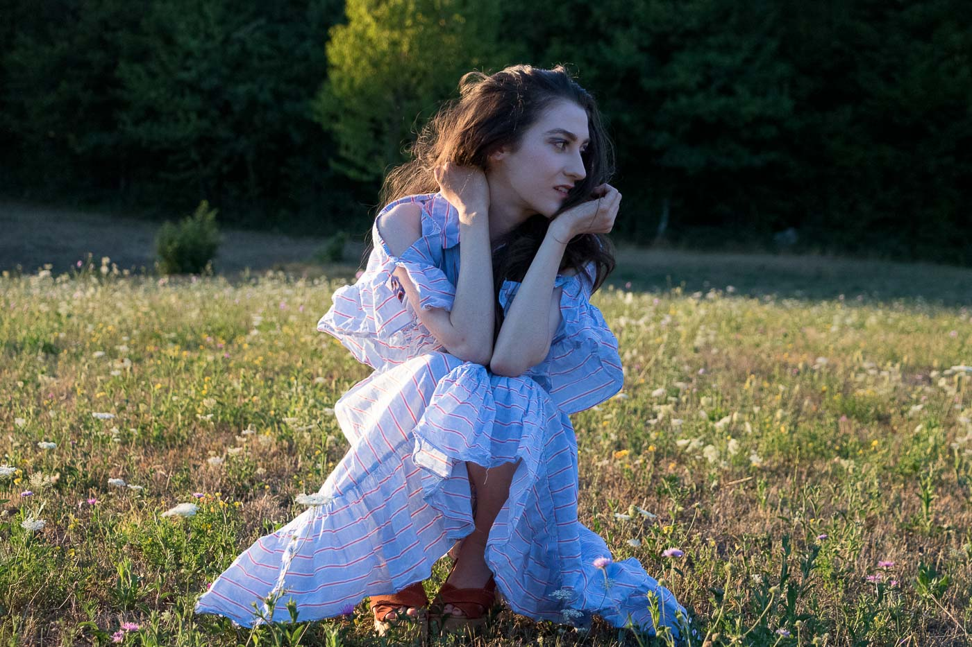 Fashion Blogger Veronika Lipar of Brunette from Wall Street wearing striped ruffled cold shoulder dress and stripes on eye lids in the golden hour on the meadow