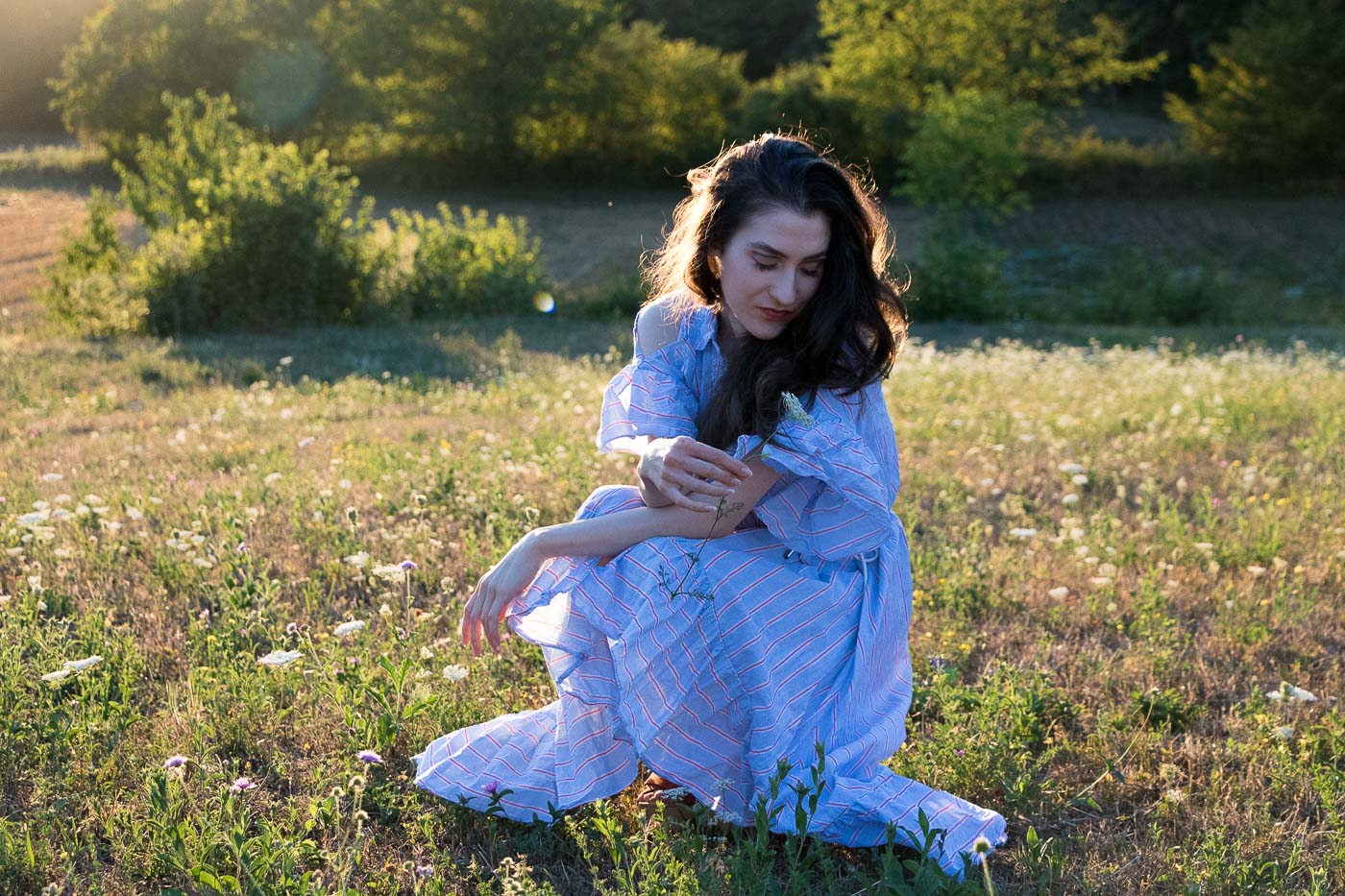 Fashion Blogger Veronika Lipar of Brunette from Wall Street wearing striped ruffled cold shoulder dress and blue eye makeup in the golden hour on the meadow