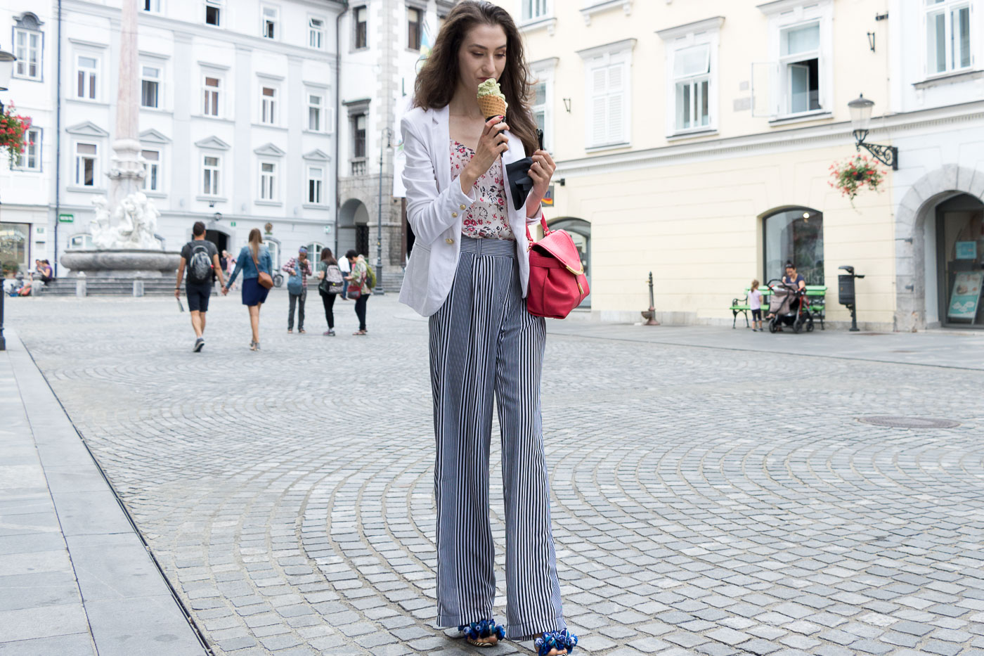 Fashion Blogger Veronika Lipar of Brunette from Wall Street eating pistachio ice cream on the street dressed in wide-leg striped Michael Kors pants, white blazer, floral slip top from Stella McCartney and blue Aquazzura sandals