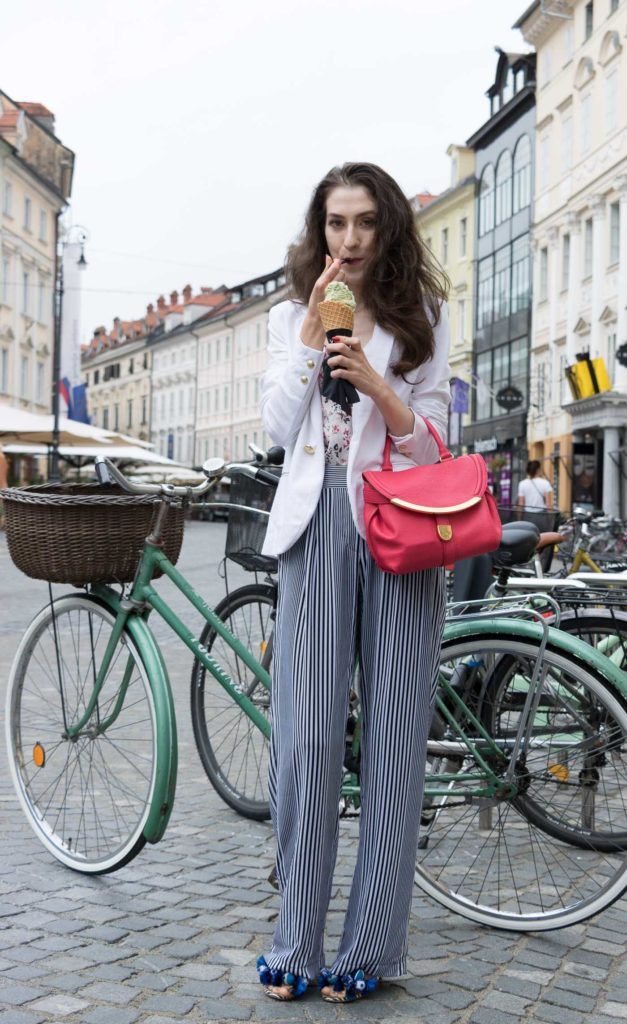 Fashion Blogger Veronika Lipar of Brunette from Wall Street eating pistachio ice cream on the street dressed in palazzo striped Michael Kors pants, white blazer, floral slip top from Stella McCartney and blue Aquazzura sandals