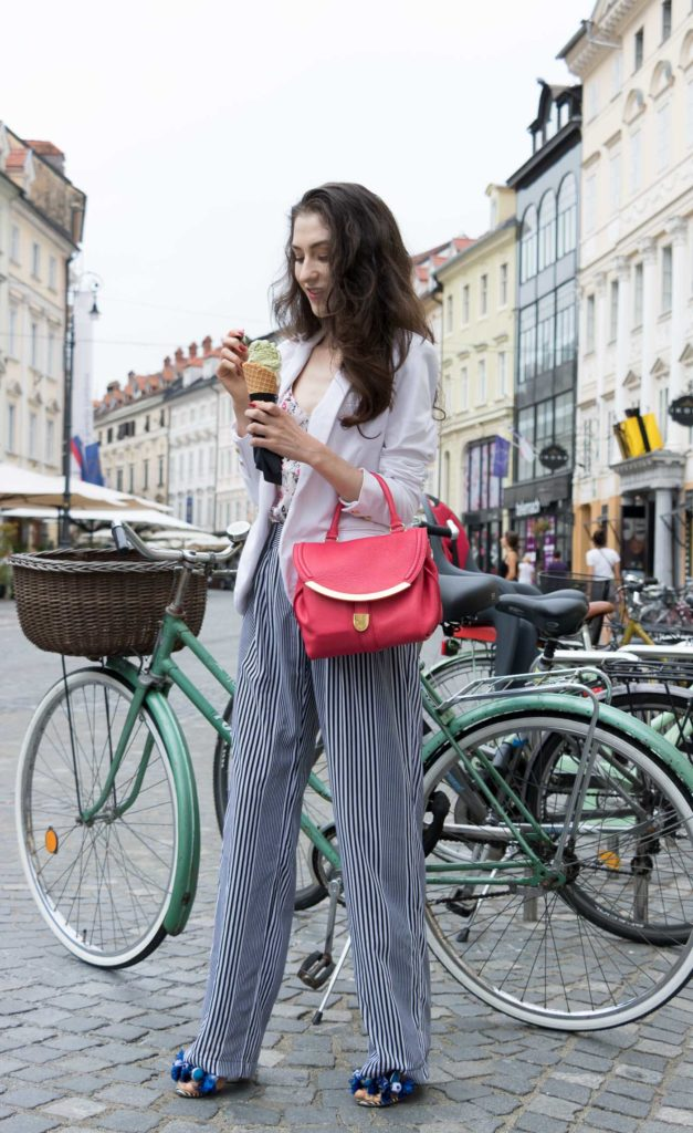 Fashion Blogger Veronika Lipar of Brunette from Wall Street eating pistachio ice cream on the street wearing palazzo striped Michael Kors trousers, white blazer, floral slip top from Stella McCartney and blue Aquazzura sandals
