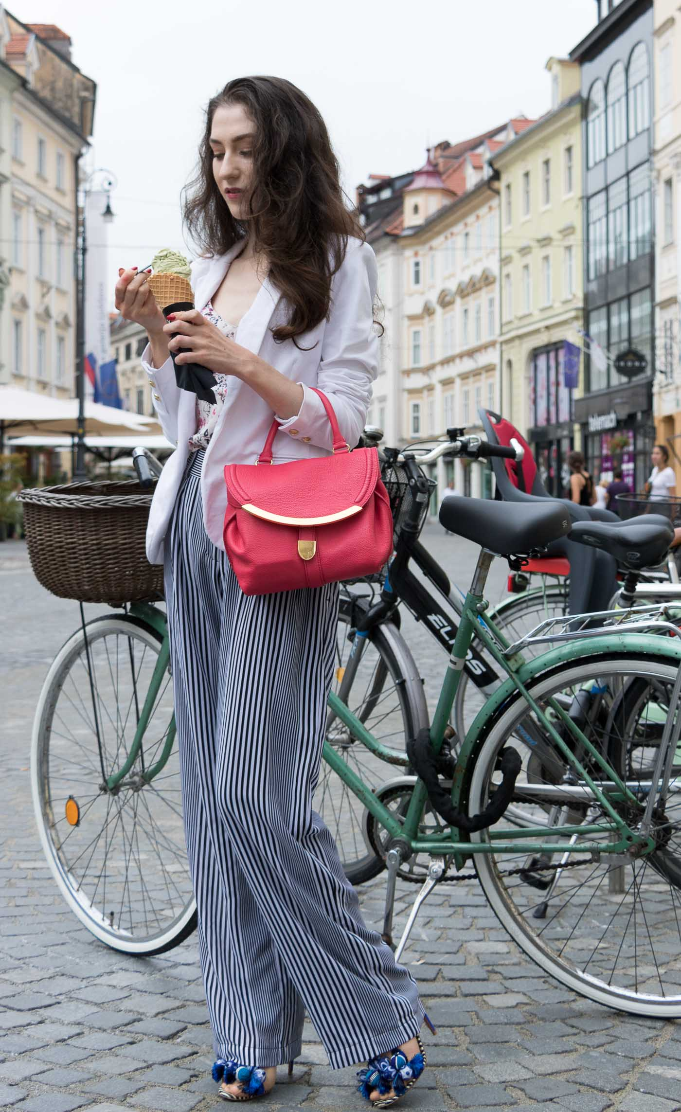 Fashion Blogger Veronika Lipar of Brunette from Wall Street eating pistachio ice cream on the street dressed in wide-leg Michael Kors pants with stripes, white blazer, floral slip top from Stella McCartney and blue Aquazzura sandals