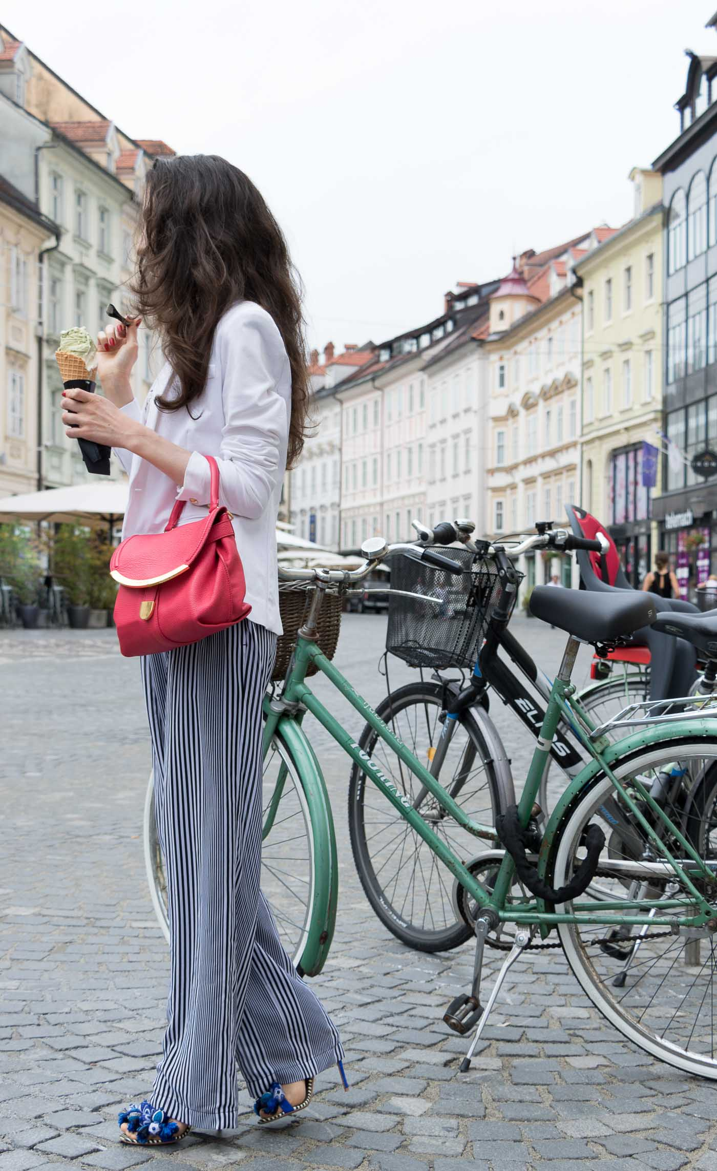 Fashion Blogger Veronika Lipar of Brunette from Wall Street eating pistachio ice cream on the street dressed in wide-leg Michael Kors trousers with stripes, white blazer, floral slip top from Stella McCartney and blue Aquazzura sandals