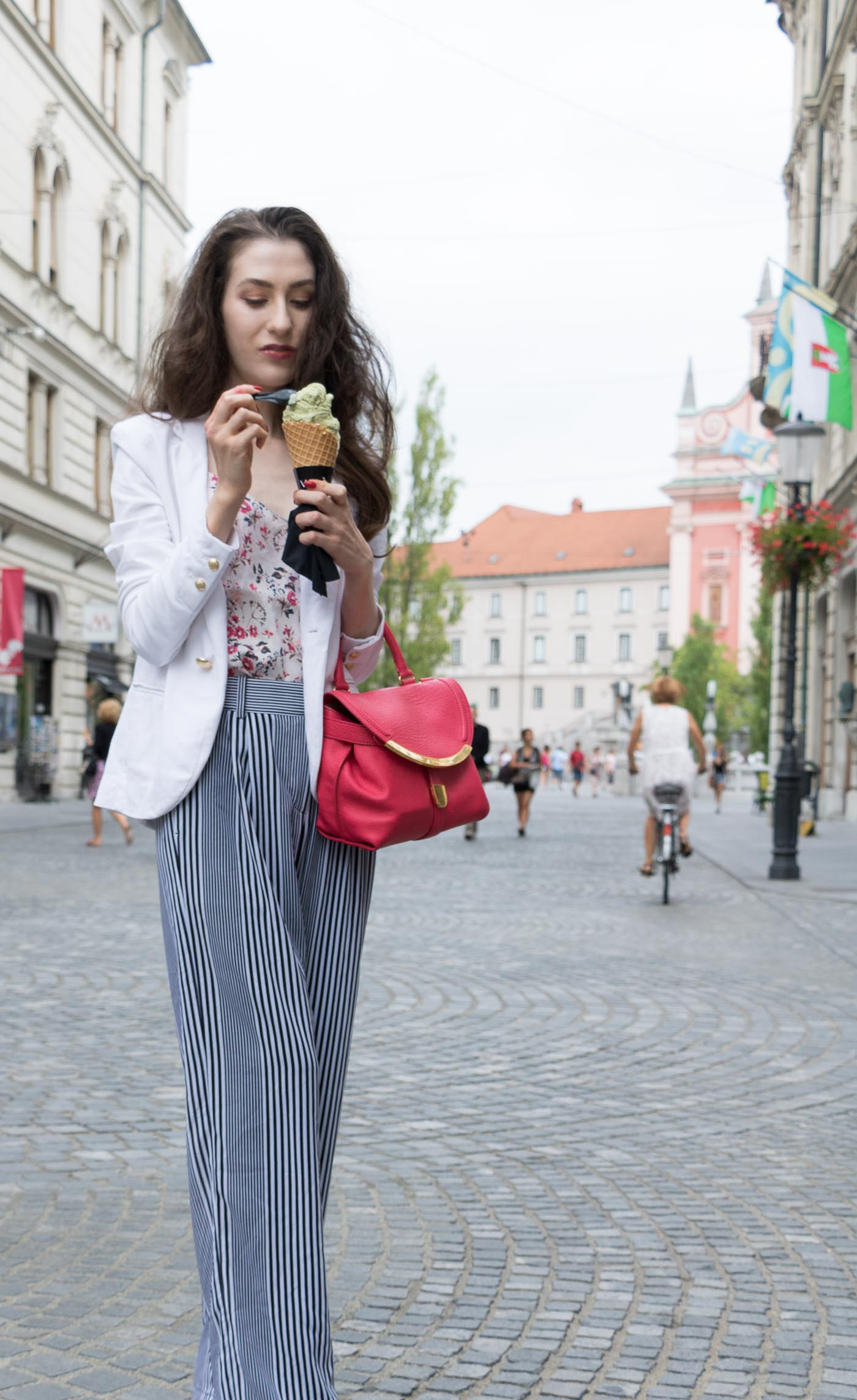 Fashion Blogger Veronika Lipar of Brunette from Wall Street eating pistachio ice cream on the street dressed in wide-leg striped Michael Kors trousers, white blazer, floral slip top from Stella McCartney and blue Aquazzura sandals