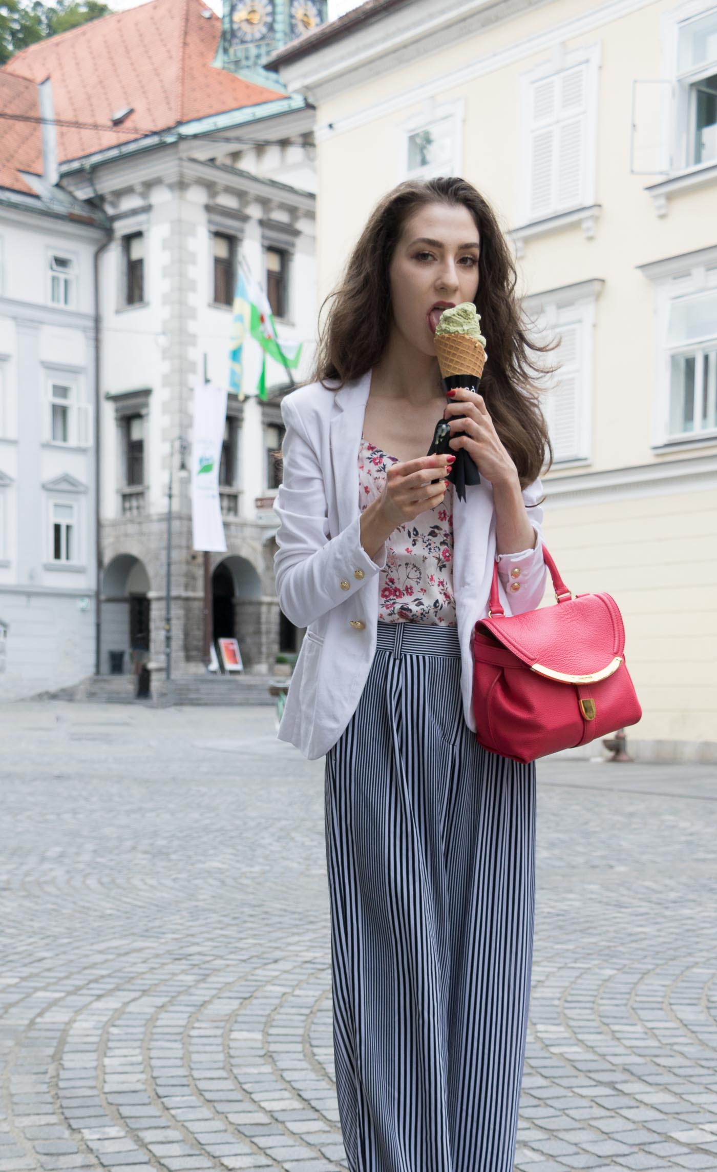 Fashion Blogger Veronika Lipar of Brunette from Wall Street eating pistachio ice cream on the street wearing wide-leg striped Michael Kors pants, white blazer, floral slip top from Stella McCartney and blue Aquazzura sandals