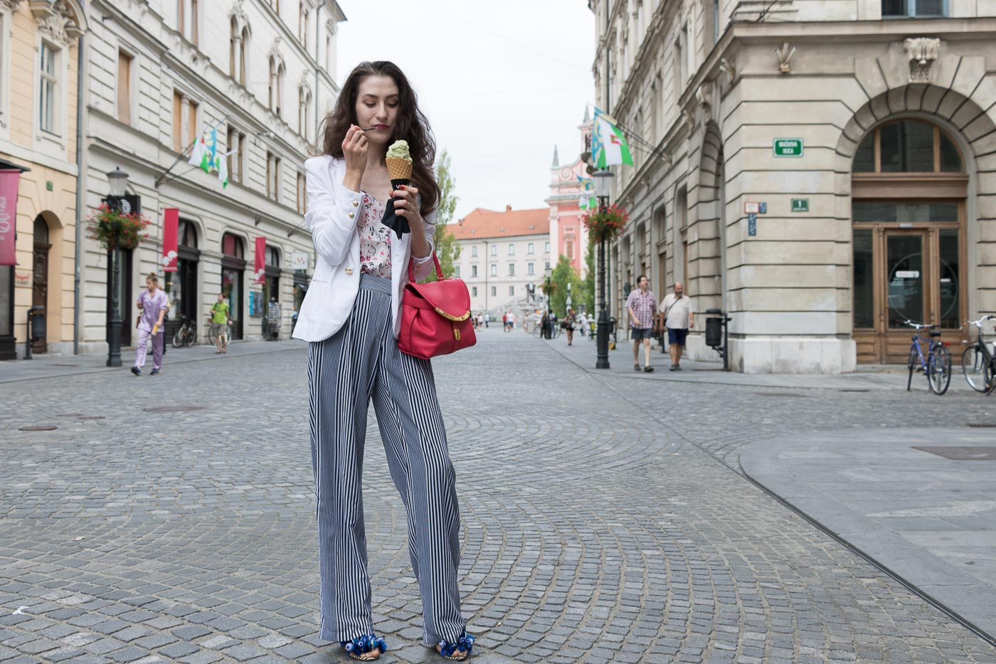 Fashion Blogger Veronika Lipar of Brunette from Wall Street eating pistachio ice cream on the street wearing palazzo striped Michael Kors pants, white blazer, floral slip top from Stella McCartney and blue Aquazzura sandals