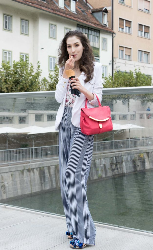 Fashion Blogger Veronika Lipar of Brunette from Wall Street eating pistachio ice cream on the street wearing wide-leg striped Michael Kors trousers, white blazer, floral slip top from Stella McCartney and blue Aquazzura sandals