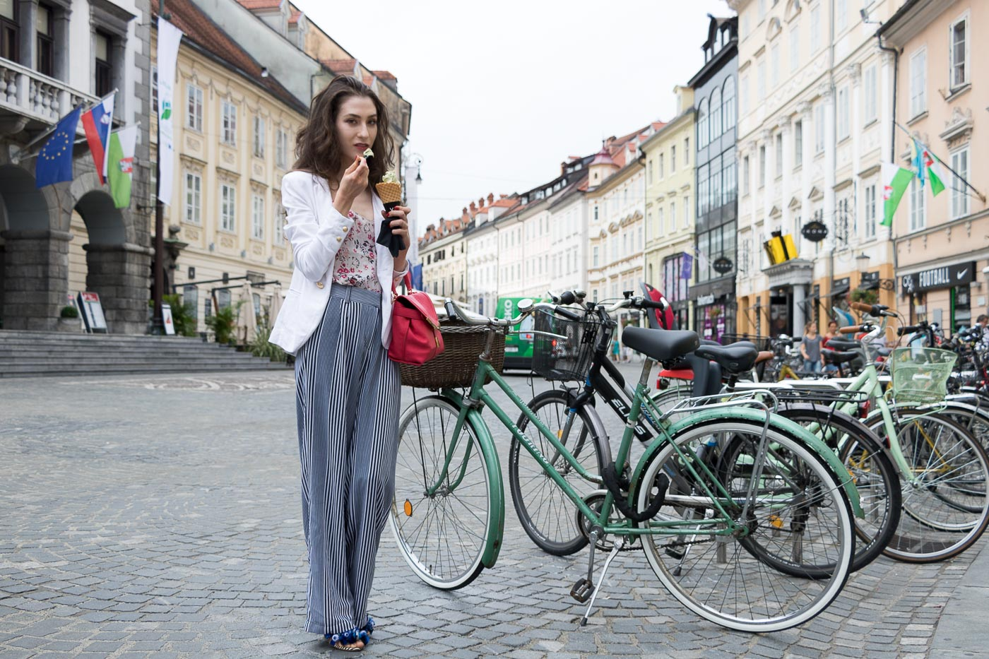 Fashion Blogger Veronika Lipar of Brunette from Wall Street eating pistachio ice cream on the street wearing wide-leg Michael Kors pants with stripes, white blazer, floral slip top from Stella McCartney and blue Aquazzura sandals