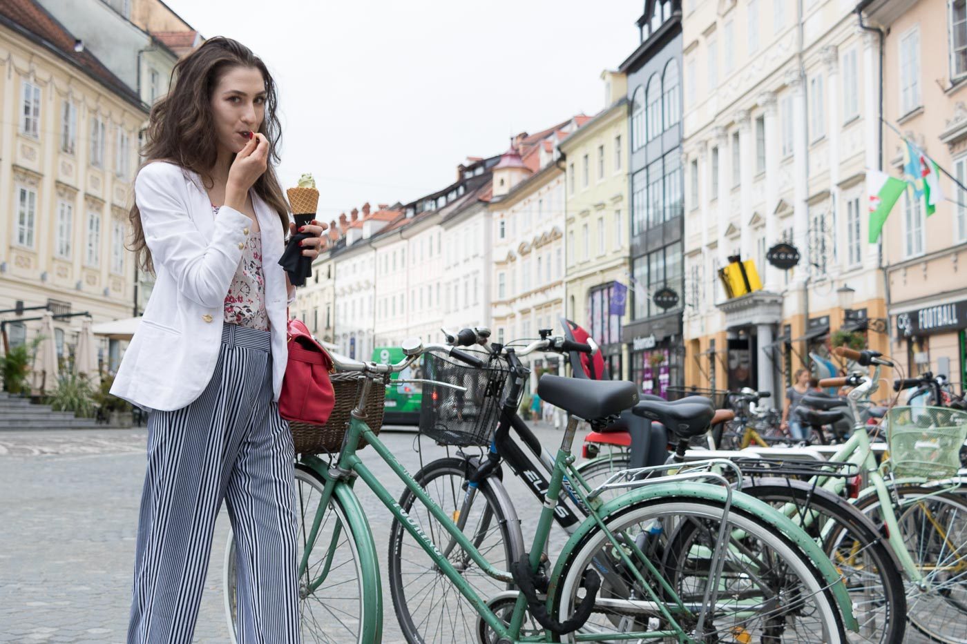 Fashion Blogger Veronika Lipar of Brunette from Wall Street eating pistachio ice cream on the street wearing wide-leg Michael Kors trousers with stripes, white blazer, floral slip top from Stella McCartney and blue Aquazzura sandals