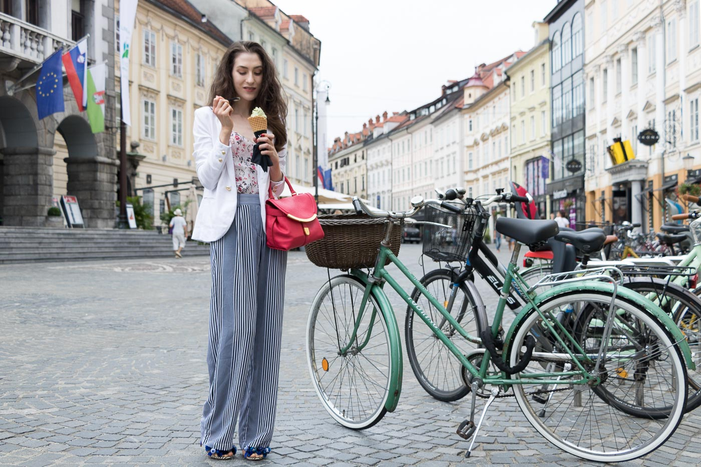 Fashion Blogger Veronika Lipar of Brunette from Wall Street eating pistachio ice cream on the street dressed in palazzo striped Michael Kors trousers, white blazer, floral slip top from Stella McCartney and blue Aquazzura sandals