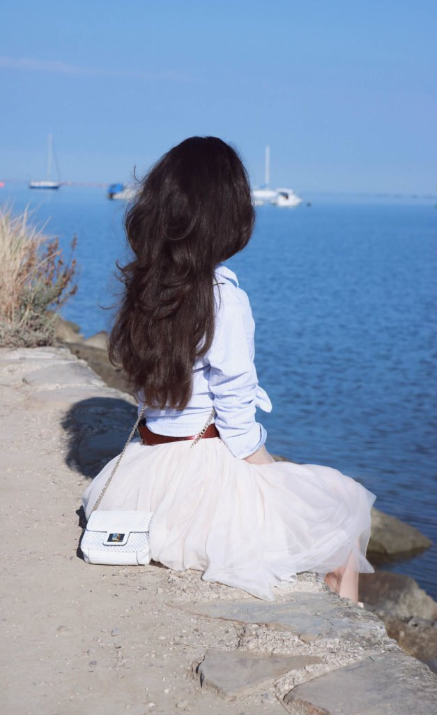 Fashion Blogger Veronika Lipar of Brunette from Wall Street sitting above the sea