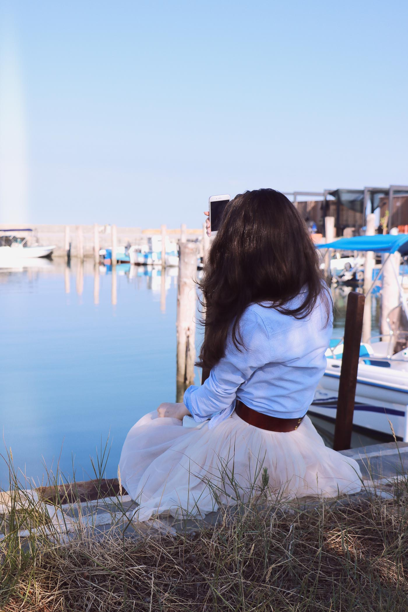 Fashion Blogger Veronika Lipar of Brunette from Wall Street standing by the sea
