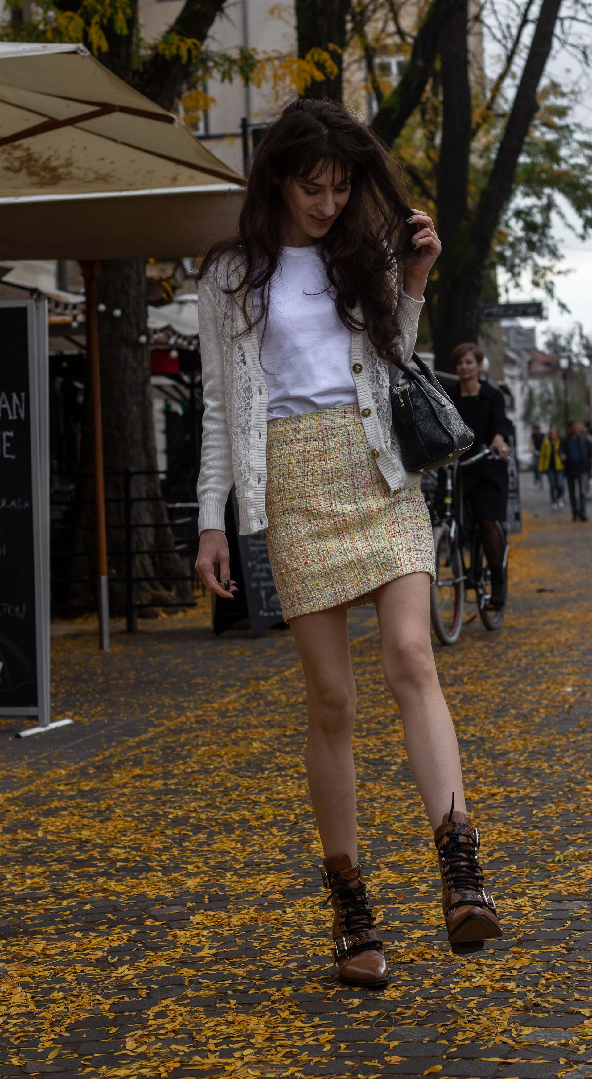 Fashion blogger Veronika Lipar of Brunette from Wall Street wearing white lace short cardigan white T-shirt yellow mini tweed skirt Chloé Rylee brown boots going to Thanksgiving Day brunch playing with the autumnal leaves before going to Thanksgiving Day brunch