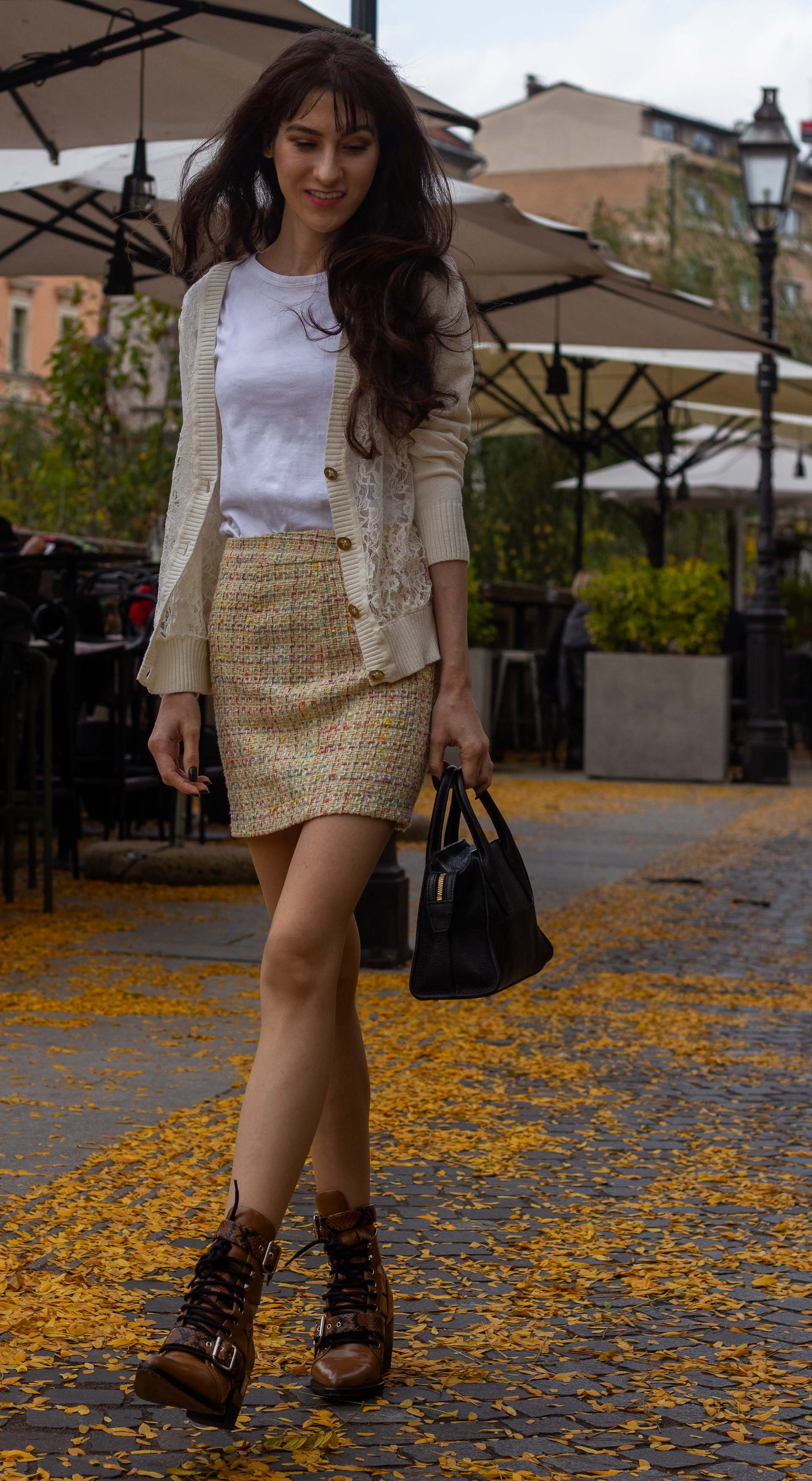Fashion blogger Veronika Lipar of Brunette from Wall Street wearing white lace short cardigan white T-shirt yellow mini tweed skirt Chloé Rylee brown boots going to Thanksgiving Day brunch walking down the street covered in leaves