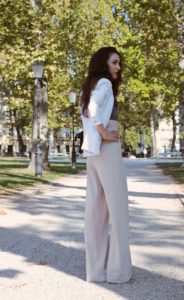 Fashion Blogger Veronika Lipar of Brunette from Wall Street walking in the park full of autumn leaves wearing wide-leg paper bag pants, blazer and small black bag