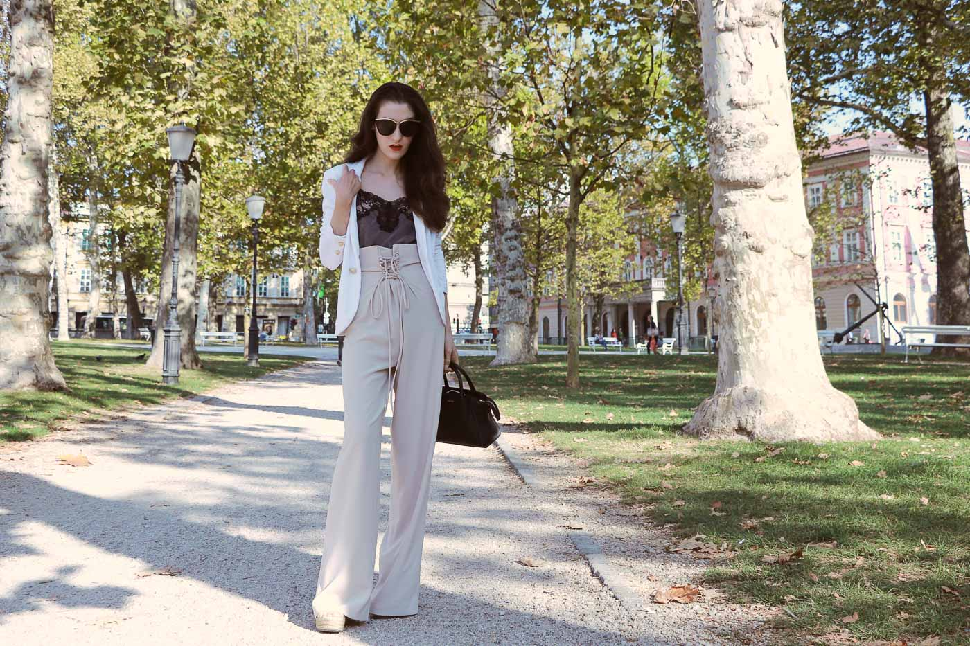 Fashion Blogger Veronika Lipar of Brunette from Wall Street dressed in wide-leg paper bag pants, blazer and small black bag