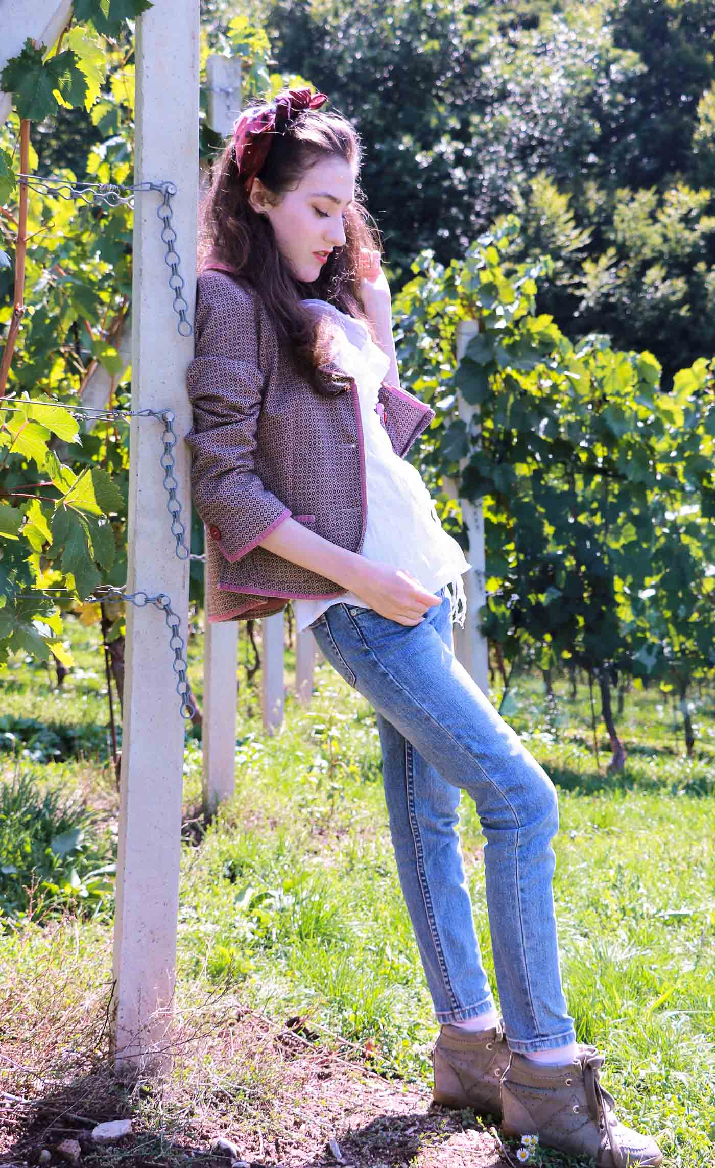 Fashion Blogger Veronika Lipar of Brunette from Wall Street in vineyard dressed in retro printed tweed blazer, blue mom jeans, bobby sneaker, head scarf, gloves