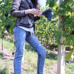 Fashion Blogger Veronika Lipar of Brunette from Wall Street wearing tweed jacket, hiking boots, blue jeans for grape vines harvest in autumn