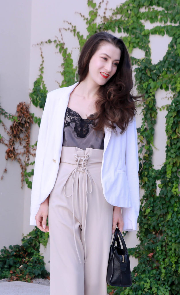 Fashion Blogger Veronika Lipar of Brunette from Wall Street wearing wide-leg paper bag pants, blazer and small black bag