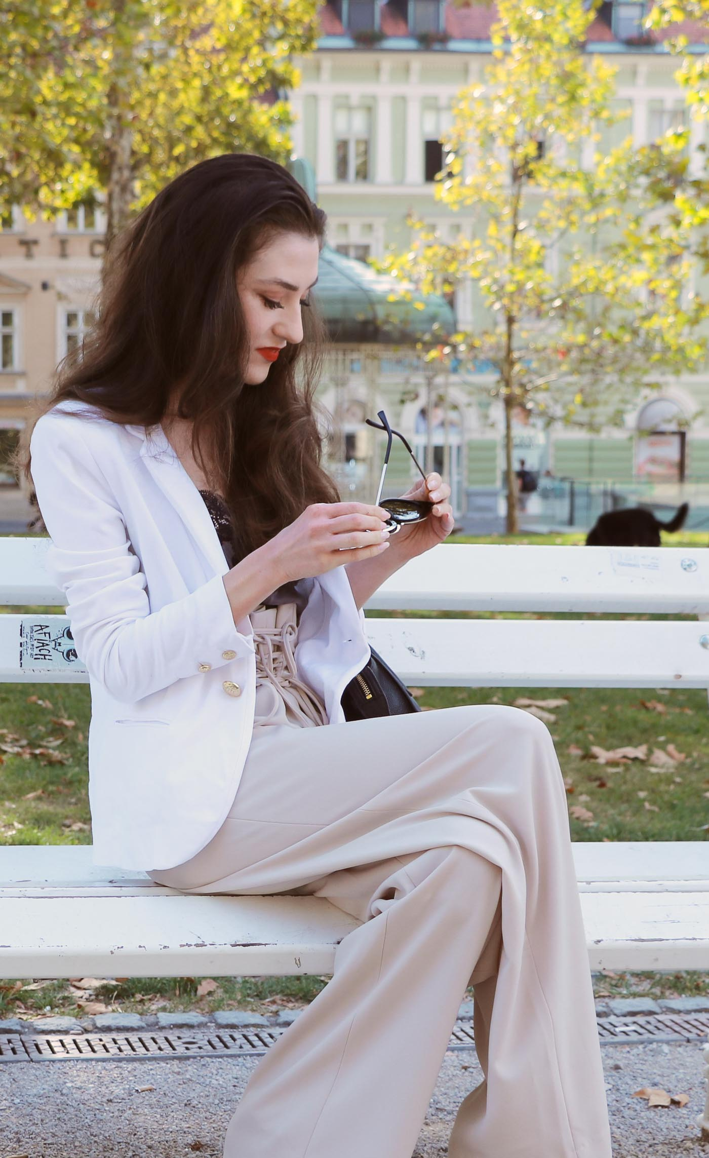 Fashion Blogger Veronika Lipar of Brunette from Wall Street sitting in the park wearing wide-leg paper bag pants, blazer and small black bag