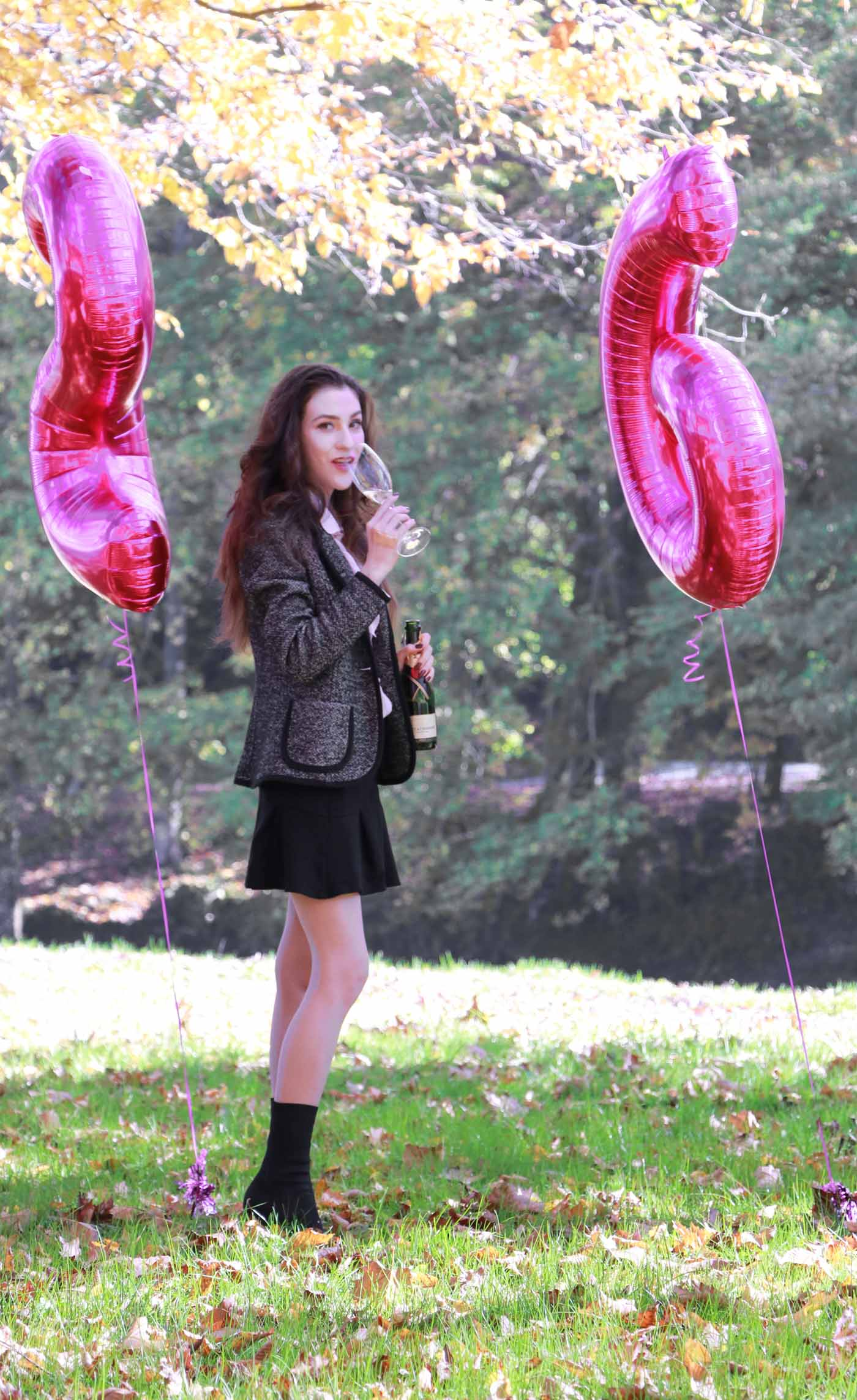 Fashion Blogger Veronika Lipar of Brunette from Wall Street playing with pink number balloons
