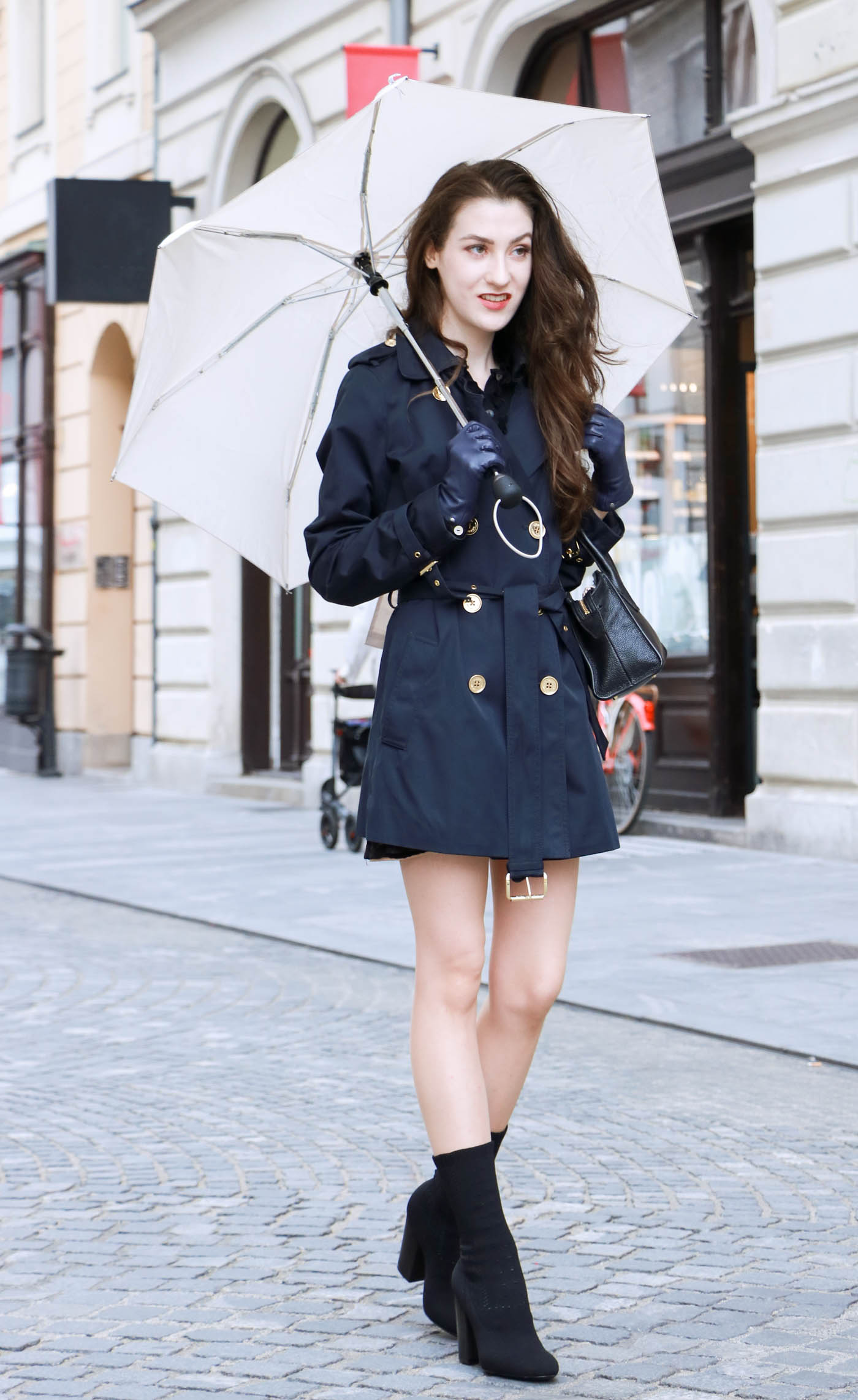 Fashion Blogger Veronika Lipar of Brunette from Wall Street wearing blue trench coat and ankle booties on a rainy day
