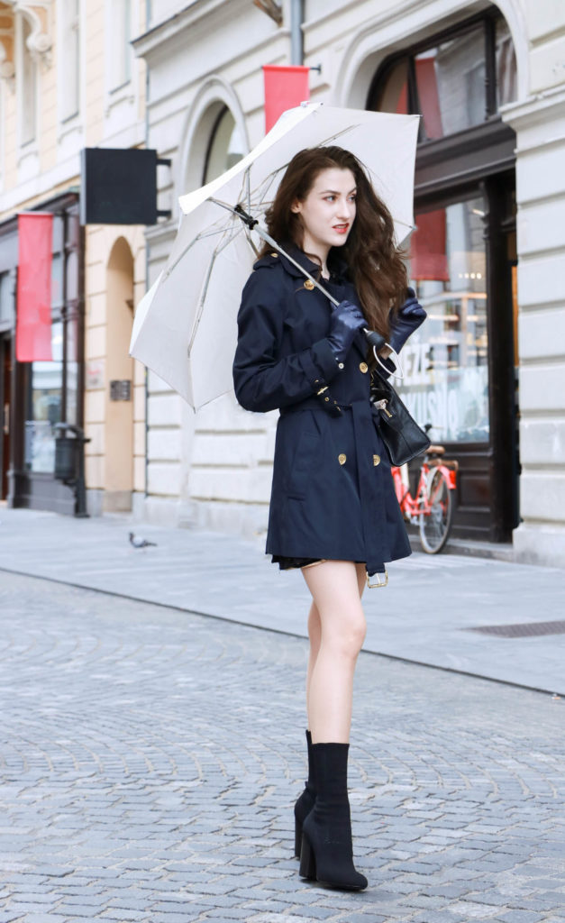Fashion Blogger Veronika Lipar of Brunette from Wall Street wearing blue trench coat and black sock booties on a rainy day