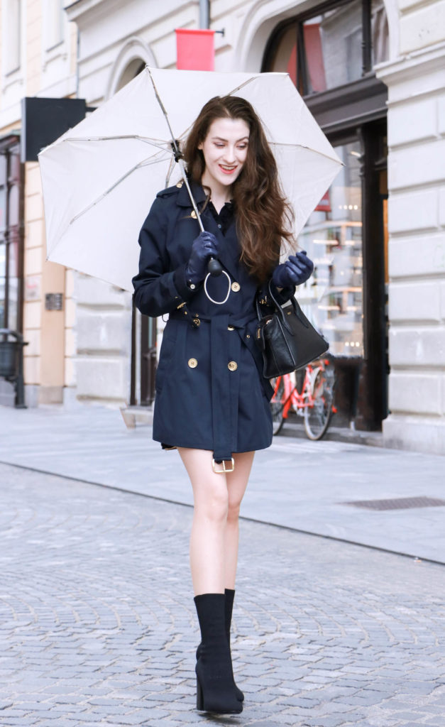 Fashion Blogger Veronika Lipar of Brunette from Wall Street wearing blue trench coat and black sock booties in the rain