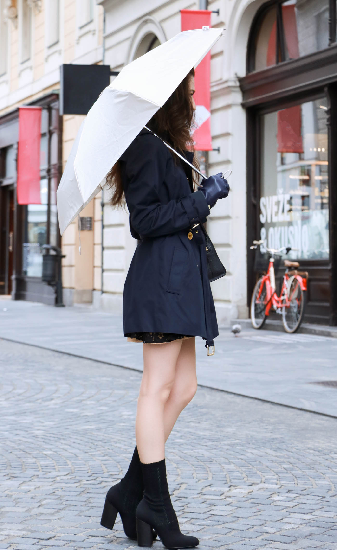 Fashion Blogger Veronika Lipar of Brunette from Wall Street wearing blue trench coat and black sock booties this autumn when rains