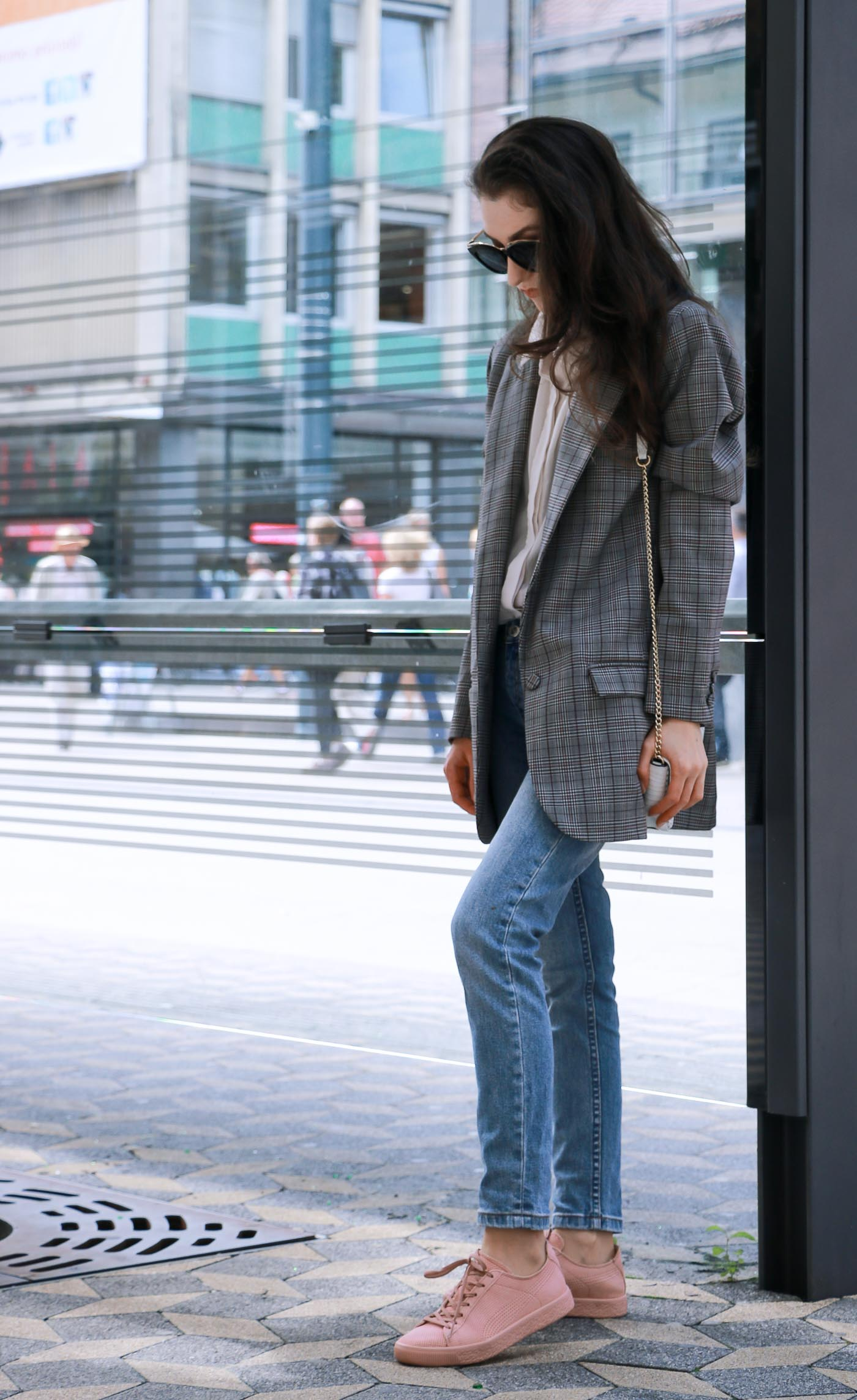 Fashion Blogger Veronika Lipar of Brunette from Wall Street wearing checked oversized boyfriend blazer and mom jeans while waiting on the bus