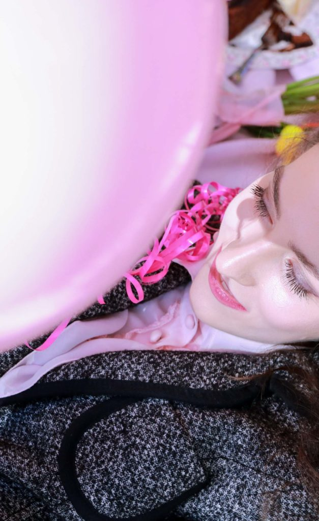 Fashion Blogger Veronika Lipar of Brunette from Wall Street laying on the pink picnic blanket playing with pink balloon